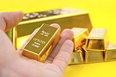 Hand hold gold bars. On yellow background Stock Photos