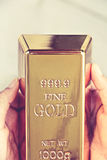 Hand hold gold bars Stock Image