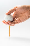 Hand hold golf ball with tee on course. Hand hold golf ball to start playing golf on white background Stock Photography