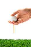 Hand hold golf ball with tee on course royalty free stock photography