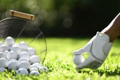 Hand hold golf ball with tee on green grass for practice royalty free stock photography