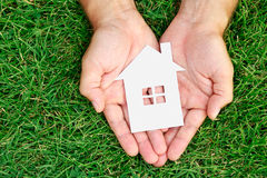 Hand hold house against green field Royalty Free Stock Photography