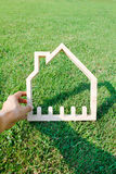 Hand hold house on green field Royalty Free Stock Images