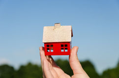Hand hold house miniature on blue sky background Royalty Free Stock Image