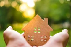 Hand hold house model on green nature background. royalty free stock photo