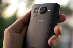 Hand hold HTC Desire HD smartphone. Hand hold a brown HTC Desire HD smartphone. Backside view Stock Photography