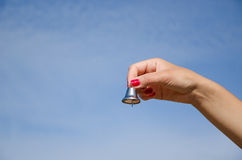 Hand hold jingle silver bell on blue sky Royalty Free Stock Photo