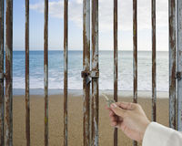Hand hold key unlocking locked door, beach, ocean, sky backgroun Stock Photography