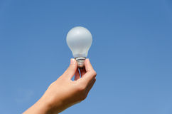 Hand hold light bulb on blue sky background Stock Photography