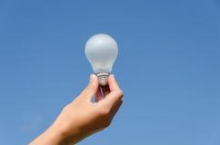 Hand hold light bulb on blue sky background Stock Photography