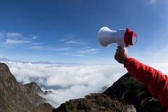 Hand hold loudspeaker. Over blue sky on mountain peak Stock Image