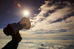 Hand hold loudspeaker to blue sky on mountain peak Stock Photos