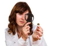 Hand hold magnifying glass and coins Stock Photo