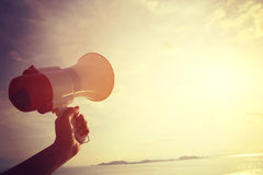 Hand hold megaphone. With sea under sky background Stock Photo