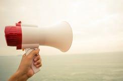 Hand hold megaphone seaside Stock Photos