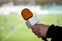Hand hold microphone for interview. During a football mach stock images