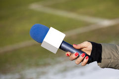Hand hold microphone for interview. On a football stadium Royalty Free Stock Photo