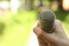Hand hold microphone. Interview in the park. Stock Images