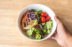 Hand hold mixed Salad bowl on wooden table Stock Photo