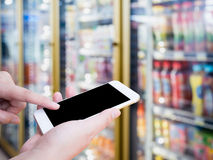 Hand hold mobile phone with blur bottles of cold drink beverage. Showing on shelves in the cold freezer at supermarket or convenience store Royalty Free Stock Image