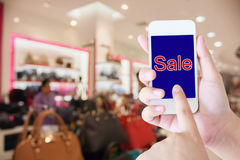 Hand hold mobile phone blurred in shopping mall background Stock Photos
