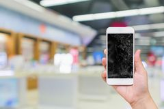 Hand hold mobile phone with broken glass screen display with abstract blur electronic shop. For smartphone fix concept stock image