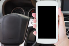 Hand hold mobile phone with car steering wheel Stock Images