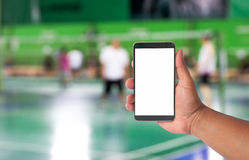 Hand hold mobile phone over blurred of badminton court with play Stock Photos