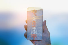 Hand hold mobile smartphone double exposure with telecom tower Royalty Free Stock Photo