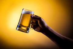 Hand hold mug of beer Stock Photo