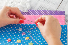 Hand hold needle sew a button Royalty Free Stock Images