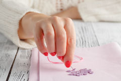Hand hold needle sew a button Royalty Free Stock Image