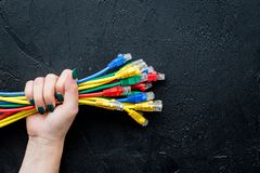 Hand hold network wires assorted colors with tips on black background top view Royalty Free Stock Images