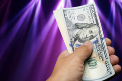 Hand hold one hundred dollar bill over beautiful lights Stock Photos