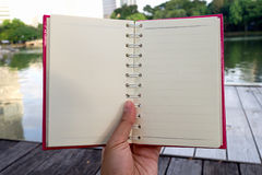 Hand hold opened white blank book with pink cover in the park and road in background Royalty Free Stock Photo