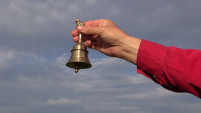 Hand hold ornamental brass bell on blue sky background stock video footage