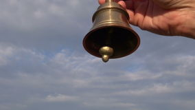 Hand hold ornamental brass bell on blue sky background stock footage