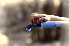 Hand hold outdoor water tap with tube Royalty Free Stock Photography