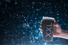 Hand hold paper cup with tea on snow background; Stock Photo