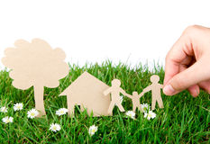 Hand hold paper cut  of family over green grass. Stock Photos