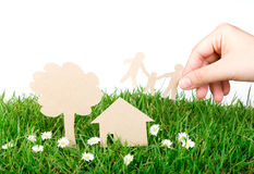 Hand hold paper cut of family over green grass Royalty Free Stock Images