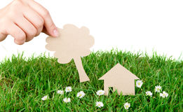 Hand hold paper cut  of House over green grass. Stock Photo