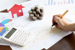 Hand hold a pen and press calculator and house paper and coins Stock Images