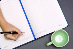 Hand hold a pen and write on a book with a cup Royalty Free Stock Photo