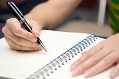 Hand hold a pen and write on a book Royalty Free Stock Images