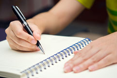 Hand hold a pen and write on a book Royalty Free Stock Photography