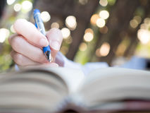 Hand hold pen for writing. In nature background Stock Image