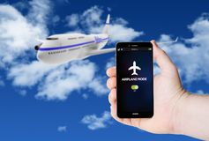 Hand hold a phone with airplane mode on the screen. Hand hold a phone with airplane mode on a screen on the background of a plane on sky. All screen graphics are royalty free stock photo