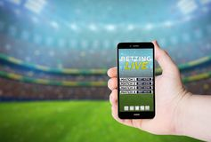 Hand hold a phone with betting online on a screen. On the background of a stadium. All screen graphics are made up royalty free stock image