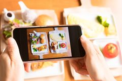 Take brunch picture. Hand hold phone take brunch picture on the table Stock Photos